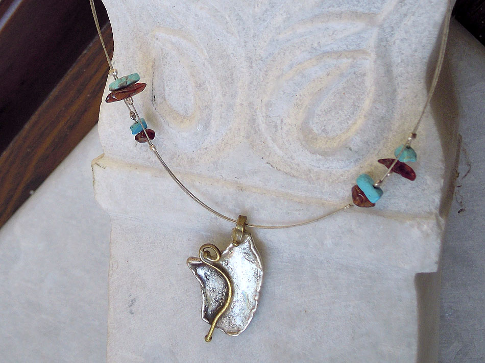 Silver pendant with bronze and stones